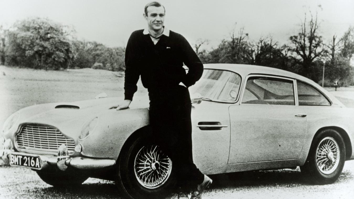 Sean Connery alias James Bond vor besagtem Aston Martin DB5.